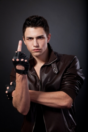 Angry handsome young man is showing a middle finger isolated on a black background photo