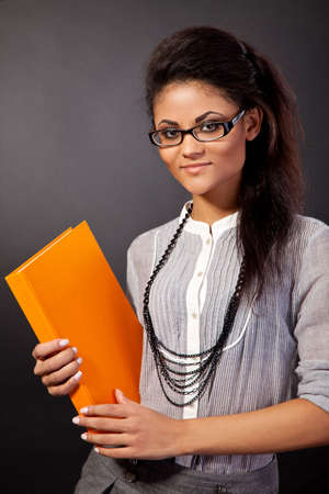 Beautiful student girl is holding an orange book isolated on black photo