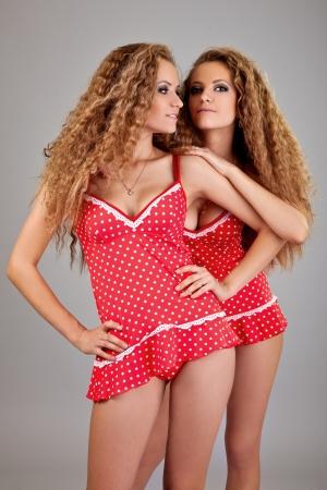 lesbianas: Dos gemelos ni�as hermosas, aislado en el fondo gris