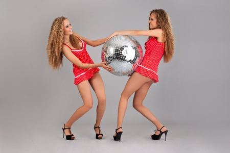 Two girls twins with glitterball, isolated on the grey background photo