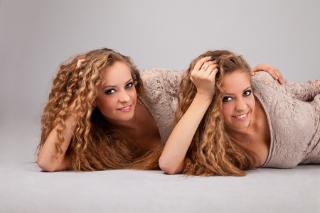 Two beautiful girls twins, isolated on the grey background Stock Photo - 13911179