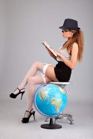 Sexy teacher holding a book isolated on grey background photo