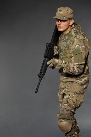 Soldier with rifle on a black background photo