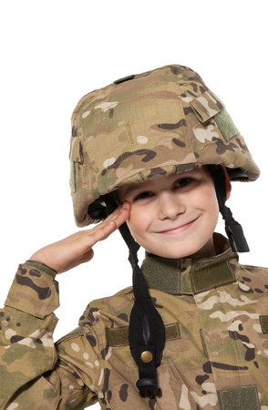 Saluting soldier. Young boy dressed like a soldier isolated on white photo