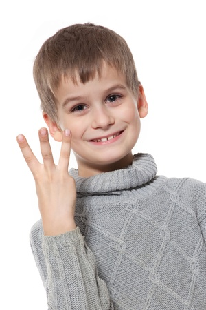 Cute boy smilling and showing three finger isolated on a white background photo