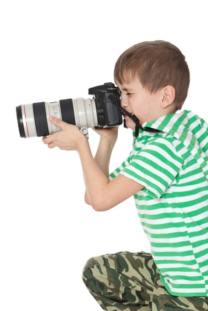 Boy holding a camera isolated on white photo