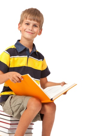 Schoolboy is sitting on books isolated on a white background photo