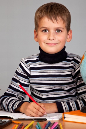 Cute schoolboy is writting isolated on a white background Stock fotó
