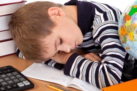 Tired schoolboy isolated on a white background photo