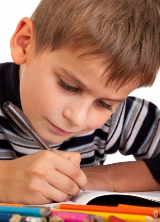 Cute schoolboy is writting isolated on a white background photo