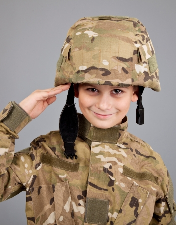 Saluting soldier. Young boy dressed like a soldier isolated on gray background photo