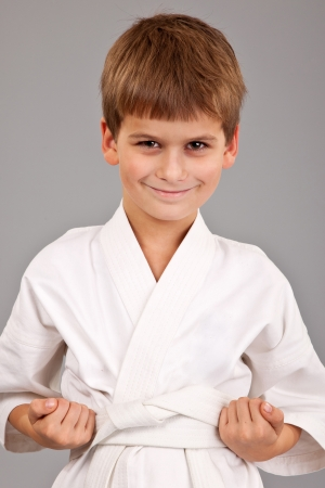 Karate boy in white kimono fighting isolated on gray background photo