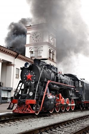 locomotora: Antiguo tren de vapor est� saliendo de una estaci�n. Motor antiguo tren de vapor locomotora bajando las v�as del tren hacia la c�mara. Editorial