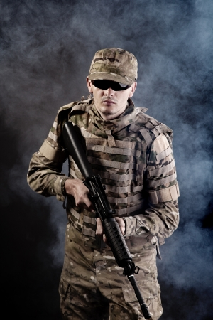 Soldier with rifle on a black background with white smoke photo