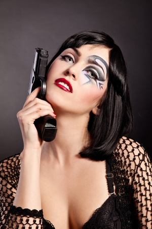 gangster girl: Beautiful woman with face art trying to make suicide isolated on black background