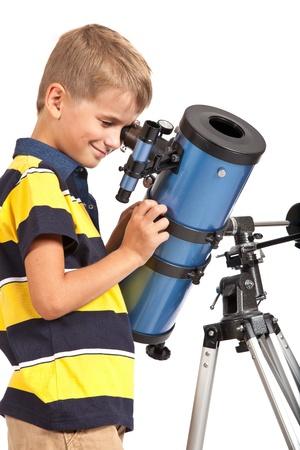 Niño que mira a Star Gazing Telescopio Little Boy aislado en un fondo blanco