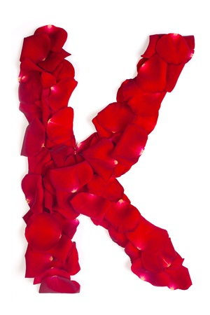 Alphabet letter K made from red petals rose isolated on a white background photo