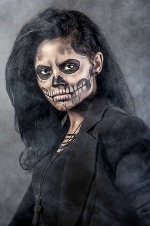 skeleton costume: Young woman in day of the dead mask skull face art. Halloween face art with fog on black background