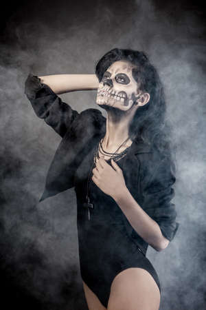 Young woman in day of the dead mask skull face art. Halloween face art with fog on black background Stock Photo - 15237989