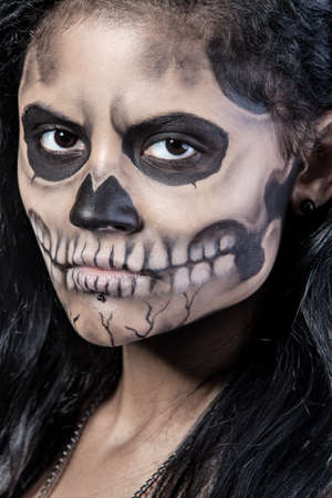 Young woman in day of the dead mask skull face art. Halloween face art with fog on black background photo