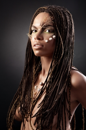 naked african: Portrait of a beautiful nude young african american woman with dreadlocks hair  on a black background