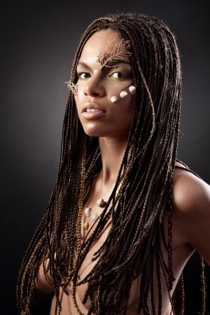 mujeres negras desnudas: Retrato de una bella mujer desnuda joven afroamericano con el pelo trenzas sobre un fondo negro Foto de archivo