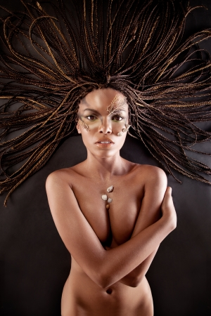 nude black women: Portrait of a beautiful naked young african american woman with dreadlocks hair lying    on a black background