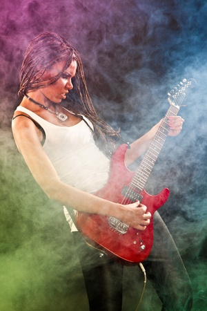 Fashion african american girl with guitar playing hard-rock. Coloured fog and light on black background photo