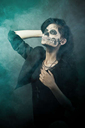 Young woman in day of the dead mask skull face art. Halloween face art with fog on black background Stock Photo - 15441041