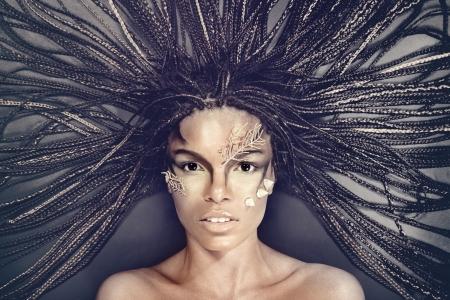 mujeres negras desnudas: Retrato de una bella mujer desnuda joven afroamericano con el pelo rastas acostado sobre un fondo negro