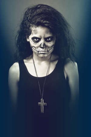 evil skull: Young woman in day of the dead mask skull face art. Halloween face art with fog on black background