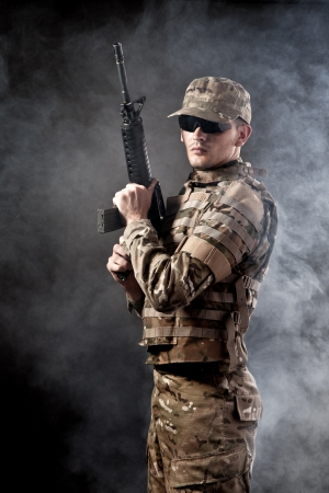 airsoft gun: Modern soldier with rifle isolated on a black background Stock Photo