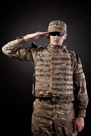 Army soldier saluting. Isolated on a black background photo