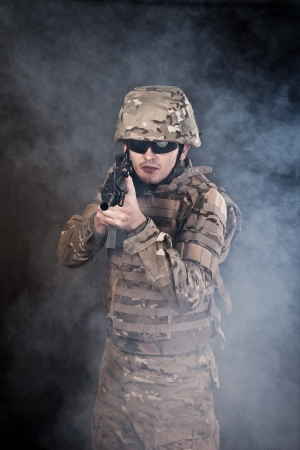 Modern soldier with rifle isolated on a black background Stock Photo - 15537621