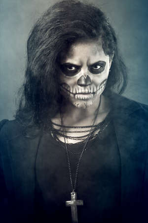 Young woman in day of the dead mask skull face art. Halloween face art with fog on black background Stock Photo - 15636736