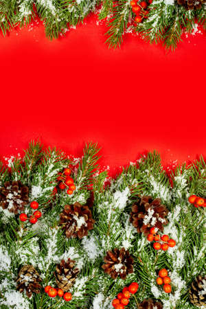Christmas green  framework, postcard with snow, cones and holly berry  isolated on red paper background photo
