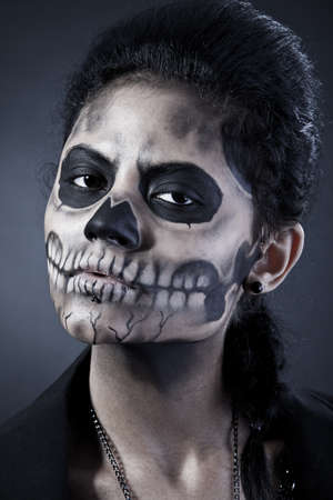 witch face: Young woman in day of the dead mask skull face art. Halloween face art with fog on black background