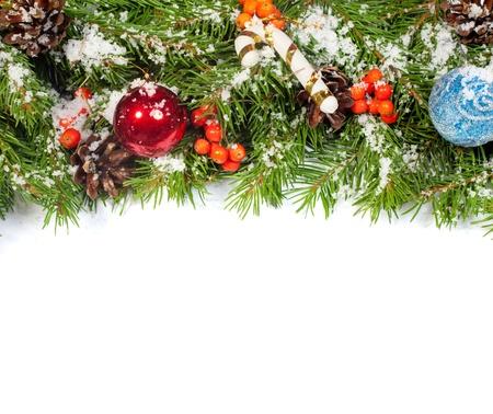 Fond de Noël avec des boules et des décorations et de la neige, houx, baies, pommes isolé sur blanc Banque d'images