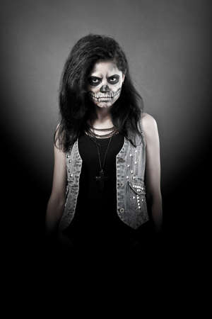 gothic girl: Young woman in day of the dead mask skull face art. Halloween face art with fog on black background