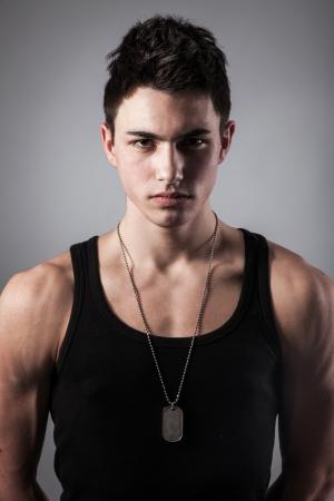 muscle shirt: Un buen aspecto integrado, muscular, hombre en un fondo negro con placas de identificaci�n.
