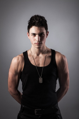 A good looking, muscular built, man on a black background with dog tags. Reklamní fotografie