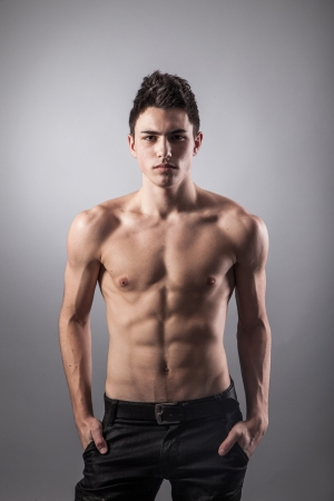 strong boy: Portrait of young bodybuilder man on a black background Stock Photo