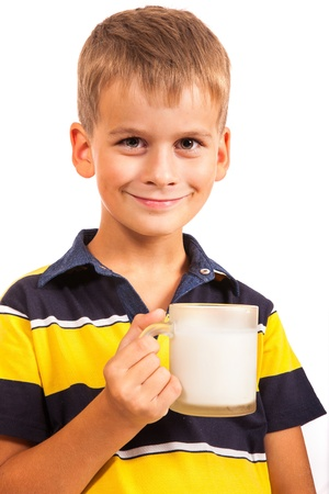 Сute boy is drinking milk. Schoolboy is holding a cup of milk isolated on a white background photo
