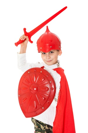Young Boy Dressed Like a knight holding a sword and shield isolated on white