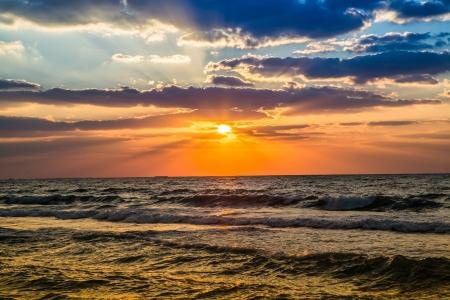 Hermosa puesta de sol en la playa, colores increíbles, haz de luz brilla a través del cloudscape sobre el paisaje marino del Golfo de Arabia, Emiratos Árabes Unidos. Dubai mar y la playa