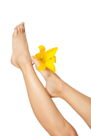 Womans Feet  and legs with flower  isolated on white. Manicure and Pedicure concept. Nails. Spa. photo
