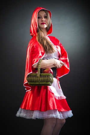 Mujer hermosa en traje de carnaval. Little Red Riding forma Hood. Aislados en negro photo