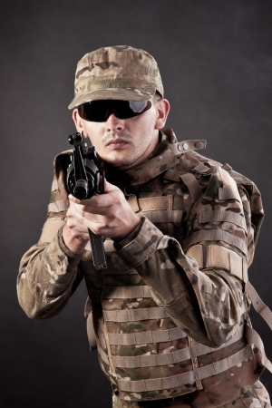 Modern soldier with rifle isolated on a black background photo