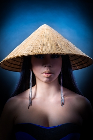 black girl nude: Beauty Portrait. Beautiful brunette Asian woman with long black hair wears vietnam hat. Shot in a studio on a black background Stock Photo