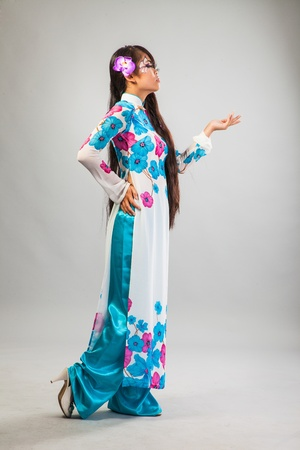 Beautiful asian woman wears a national dress isolated on a grey backround photo
